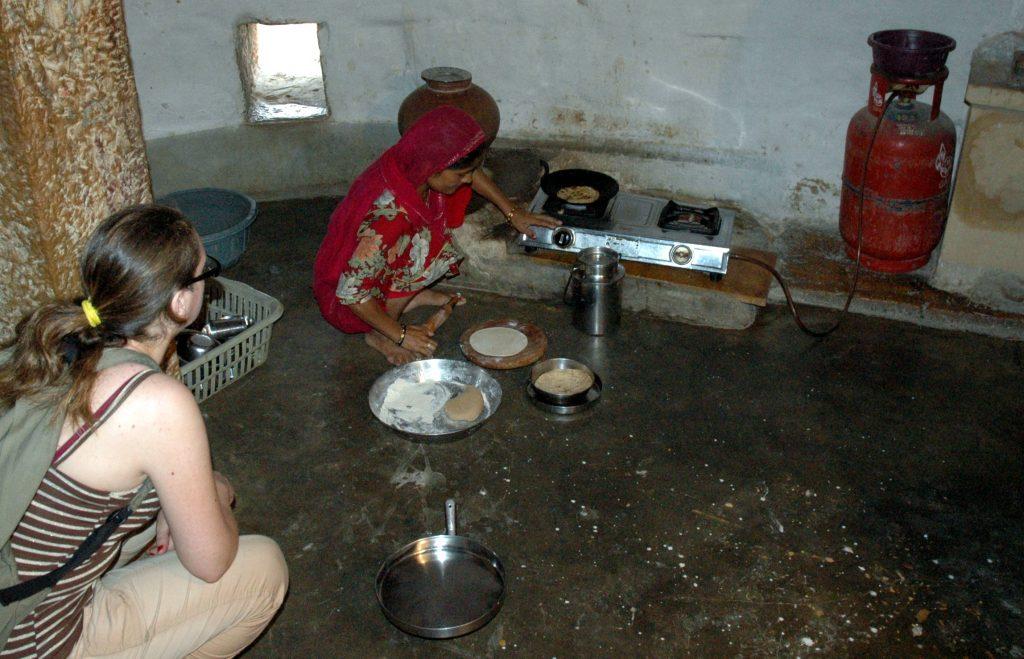 Jaisalmer, una donna cucina il pane indiano roti con il tawa